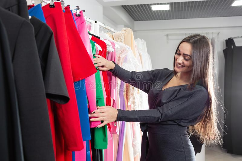 Lycklig ung kvinna som väljer kläder i galleria eller bekläda lager Sale mode, consumerismbegrepp arkivbild