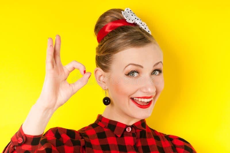 Lycklig ung kvinna som visar det ok tecknet med fingrar på en gul backg arkivfoto