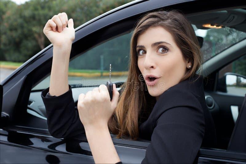 Lycklig ung kvinna som visar stor glädje med ny bilinnehavtangent arkivfoton