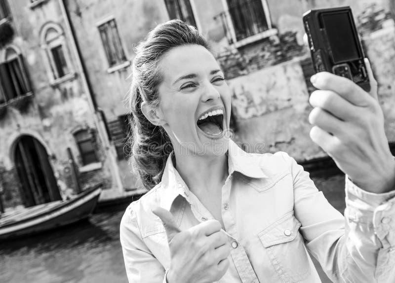 Lycklig ung kvinna som visar upp tummar och gör selfie i venice, arkivbilder