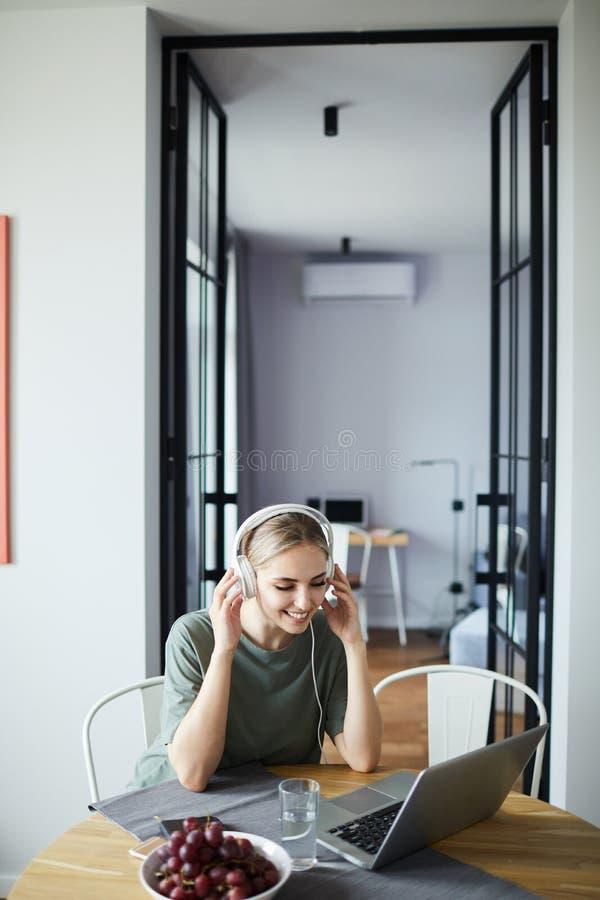 Lycklig ung kvinnlig i hörlurar som påverkar varandra till och med video-pratstund royaltyfria foton