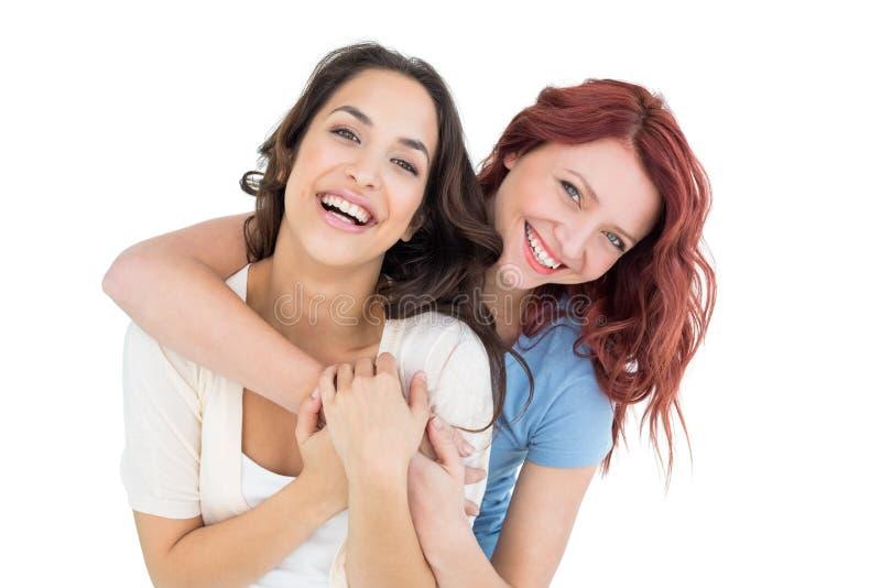 Lycklig ung kvinnlig som bakifrån omfamnar hennes vän arkivfoto