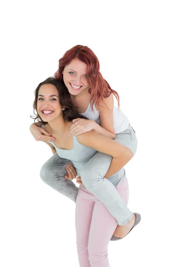 Lycklig ung kvinnlig som piggybacking den gladlynta vännen arkivfoto