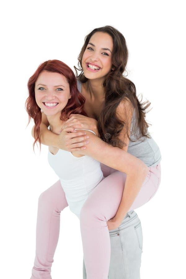 Lycklig ung kvinnlig som piggybacking den gladlynta vännen royaltyfri fotografi