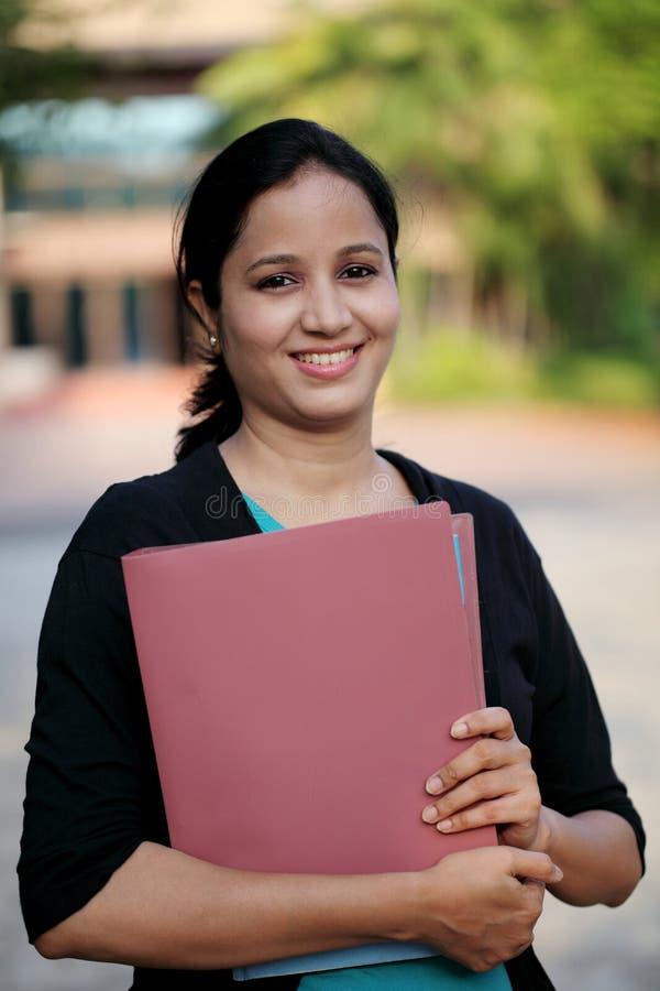 Lycklig ung kvinnlig student på högskolauniversitetsområdet arkivbild
