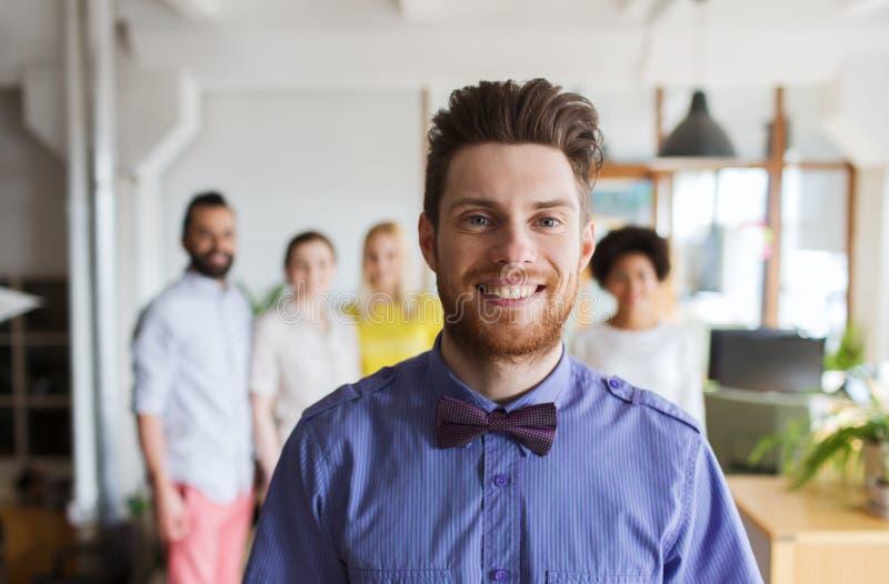 Lycklig ung man över det idérika laget i regeringsställning royaltyfria bilder