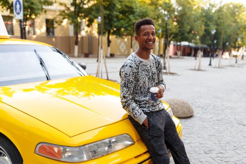 Lycklig ung man ett blandat lopp som rymmer i hand ett koppkaffe som placeras p? en gul bil f?r huv, p? en gatabakgrund arkivbild
