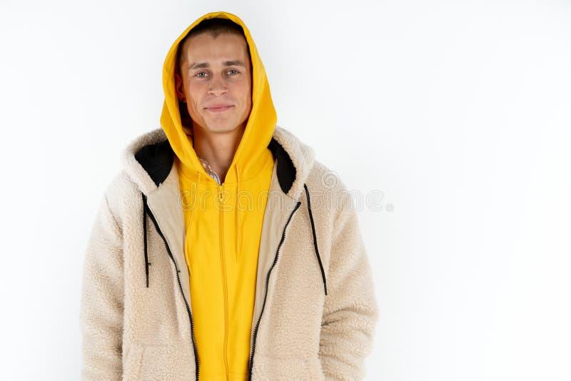 Lycklig ung man i den gula hoodien som isoleras ?ver vit bakgrund, copyspace f?r din text arkivfoto