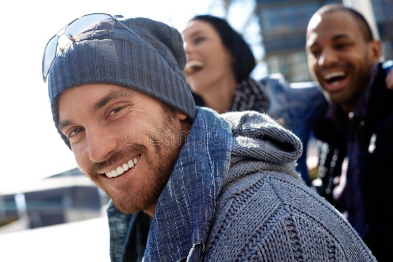Lycklig ung man i hatt och scarf arkivfoto