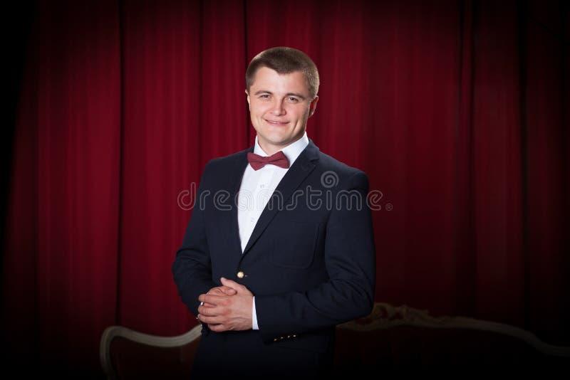 Lycklig ung man i omslag och bowtie arkivbild