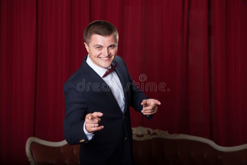 Lycklig ung man i omslag och bowtie som uttrycker positivity royaltyfri bild