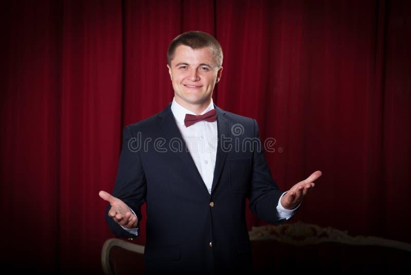 Lycklig ung man i omslag och bowtie som uttrycker positivity royaltyfria bilder