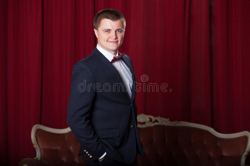 Lycklig ung man i omslag och bowtie som uttrycker positivity royaltyfri fotografi