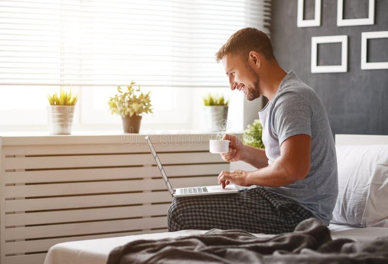 Lycklig ung man med bärbara datorn och koppen kaffe i säng royaltyfria bilder