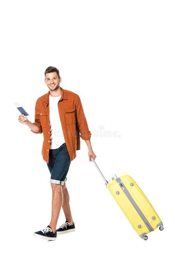 lycklig ung man med bagage och flygbiljett som går och ser kameran fotografering för bildbyråer