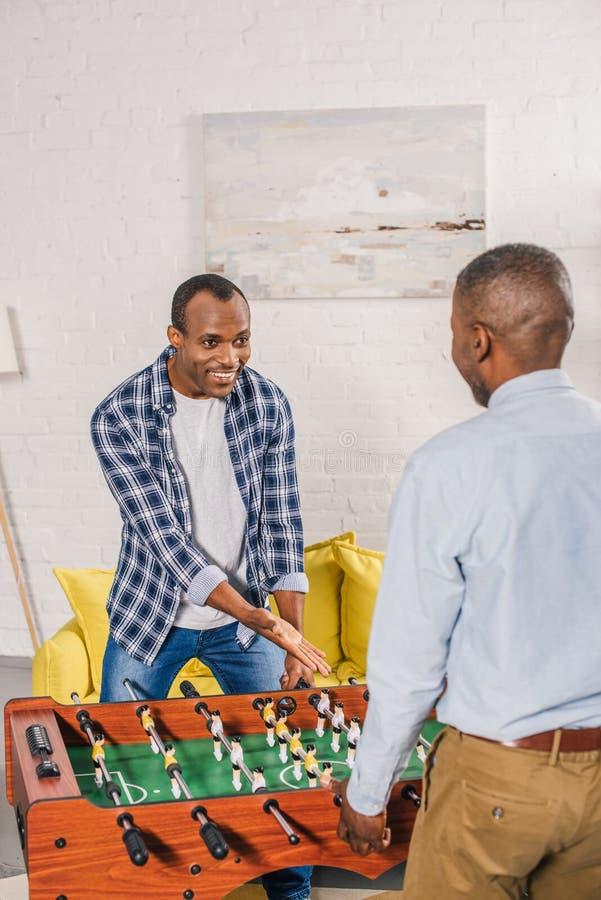 lycklig ung man med den höga fadern som spelar tabellfotboll royaltyfria foton