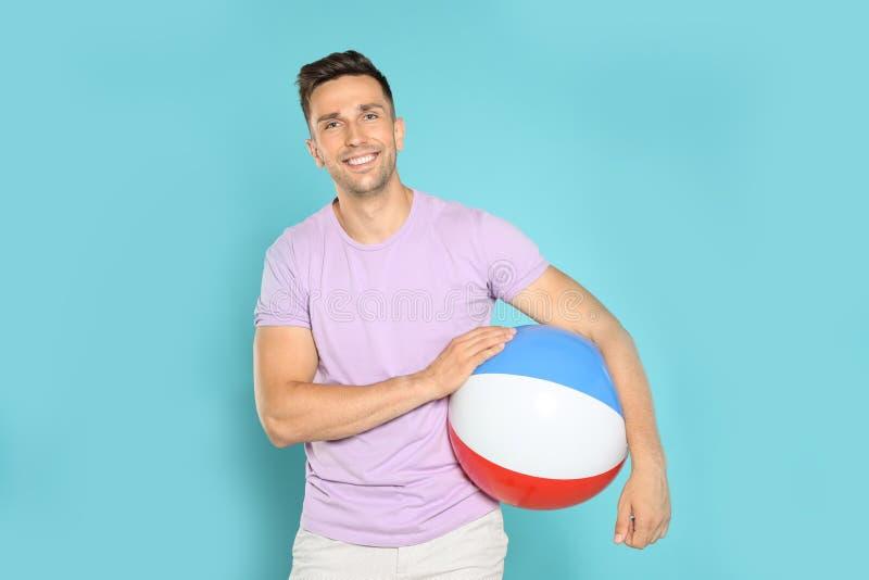 Lycklig ung man med den ljusa uppblåsbara bollen på blått arkivfoto