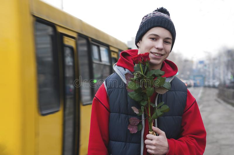 Lycklig ung man med en bukett av rosor på en stadsgata arkivfoton
