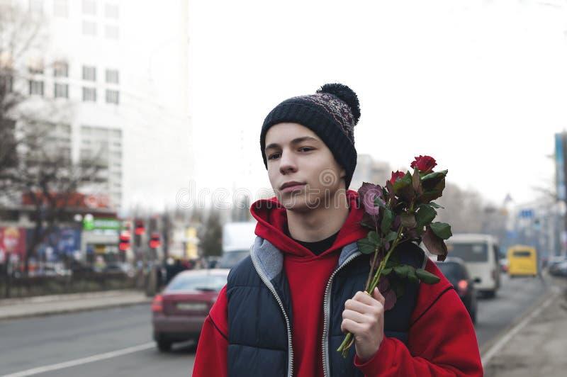 Lycklig ung man med en bukett av rosor på en stadsgata royaltyfria foton