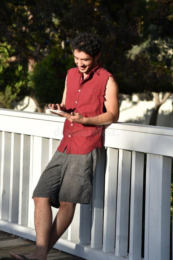 Lycklig ung man med en minnestavladator arkivfoto