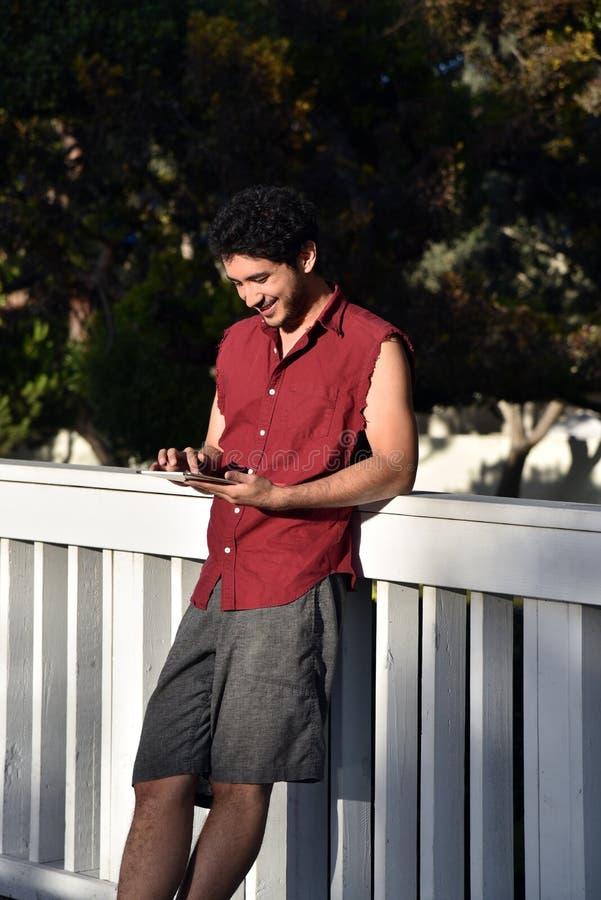 Lycklig ung man med minnestavladatoren royaltyfri fotografi