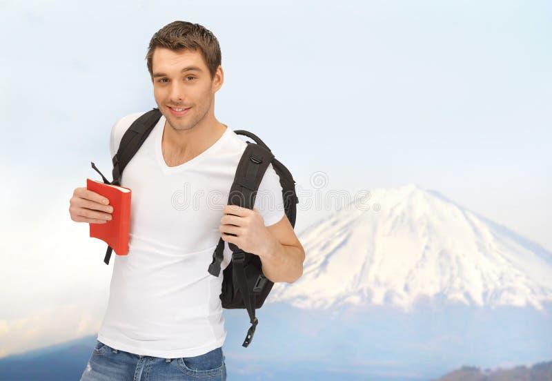 Lycklig ung man med ryggsäck- och bokresande arkivbilder