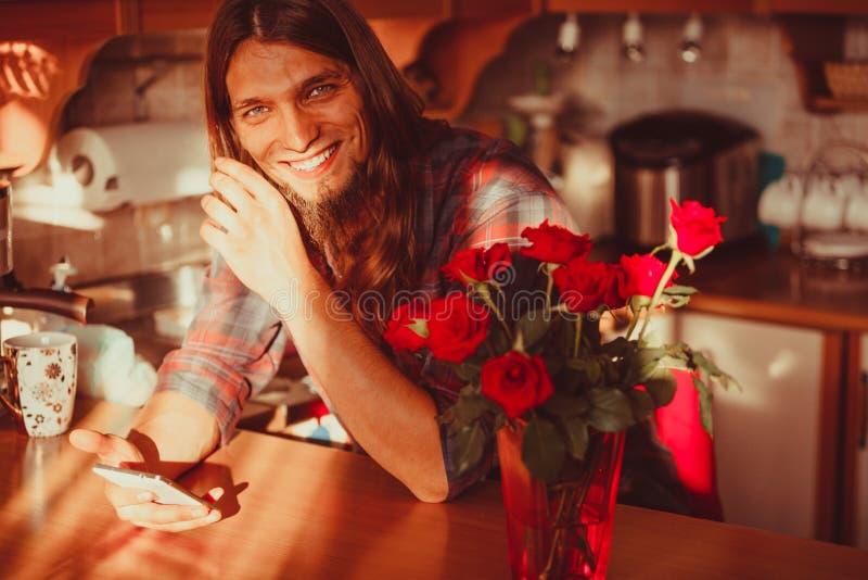 Lycklig ung man med smartphonen och rosor royaltyfri fotografi