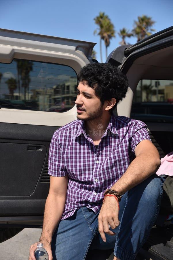 Lycklig ung man p? bakluckan av hans SUV arkivfoto