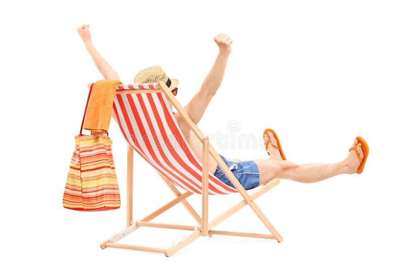 Lycklig ung man på en strandstol som gör en gest lycka royaltyfria foton