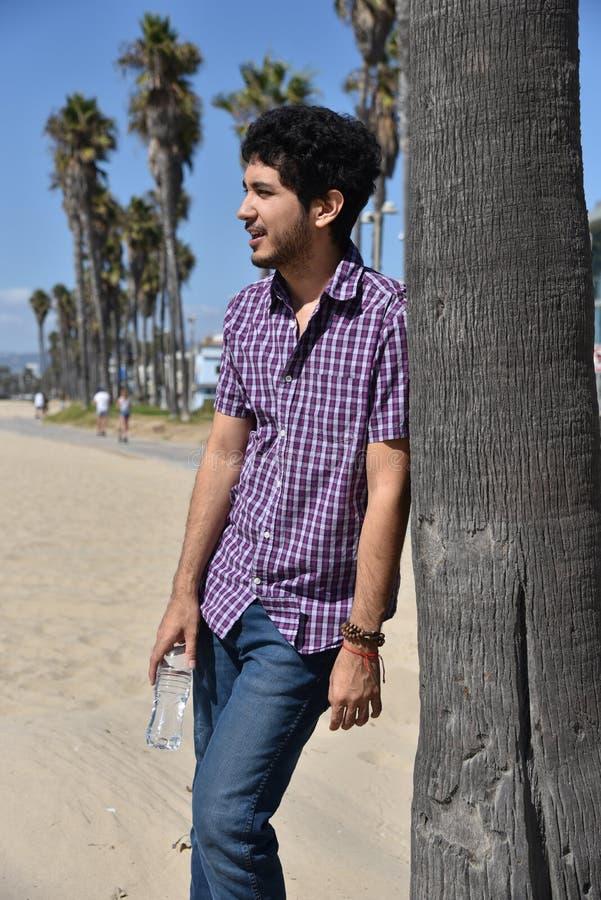 Lycklig ung man p? semester p? stranden fotografering för bildbyråer