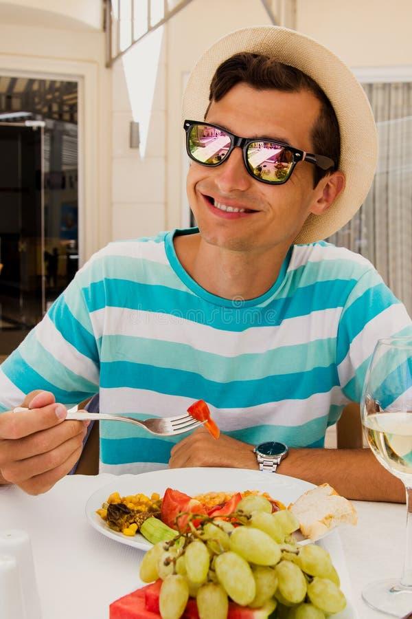 Lycklig ung man som äter mat i hotellrestaurang Allt inklusive begrepp för sommarterritorium för katya krasnodar semester royaltyfri fotografi