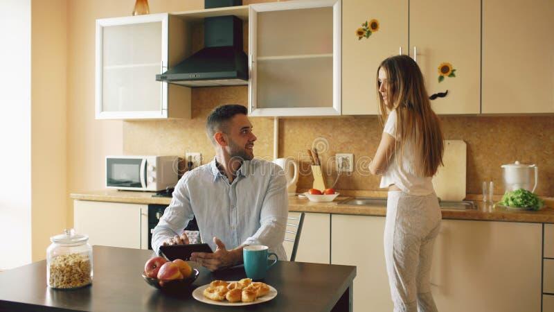 Lycklig ung man som använder digitalt minnestavladatorsammanträde i köket och talar hans fru medan henne som hemma lagar mat arkivfoto