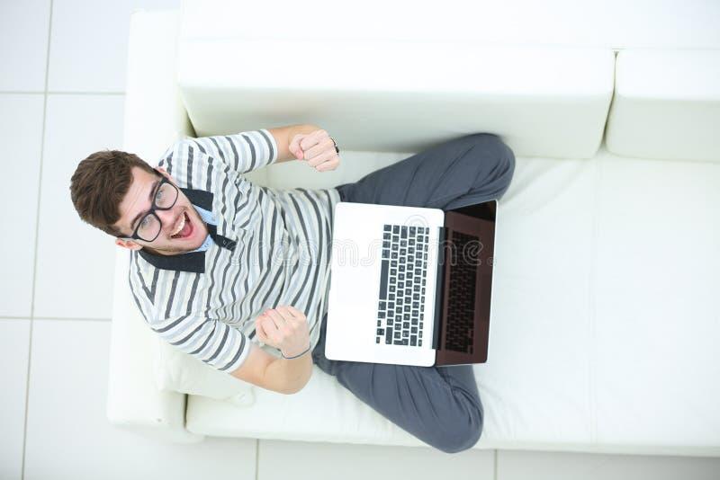 Lycklig ung man som använder upp hans bärbar dator, slut arkivfoton