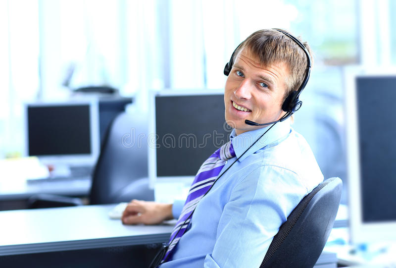 Lycklig ung man som arbetar på callcenter royaltyfri fotografi