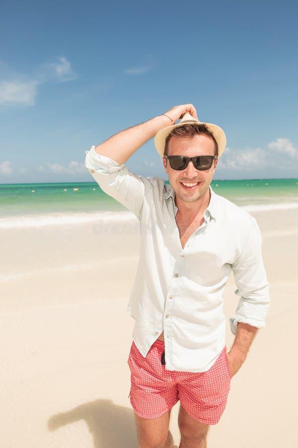 Lycklig ung man som går på stranden royaltyfri bild