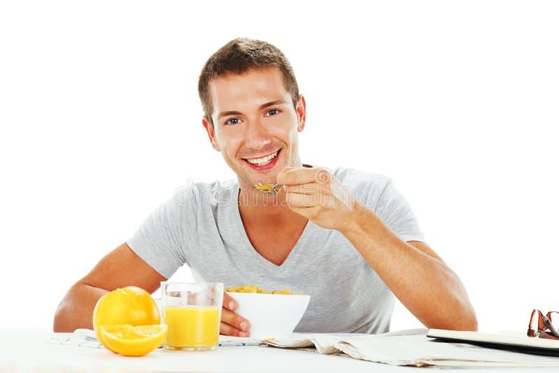 Lycklig ung man som har den driftiga frukosten royaltyfria foton