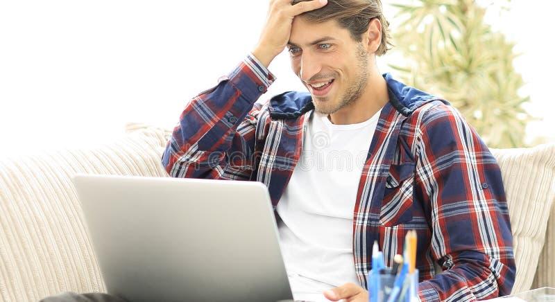 Lycklig ung man som hemifrån arbetar med bärbara datorn arkivfoton