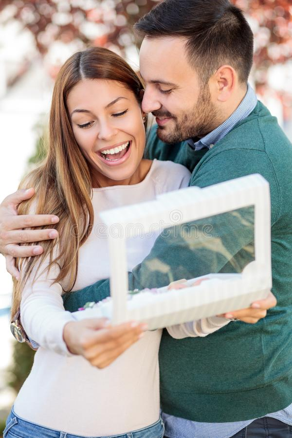 Lycklig ung man som kramar hans fru eller flickvän Kvinnan ler, når han har öppnat en gåvaask royaltyfri bild