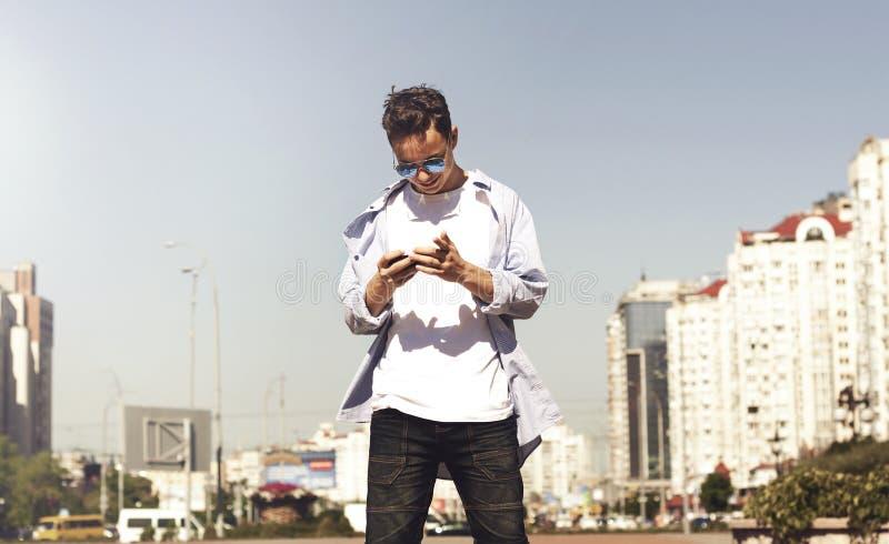 Lycklig ung man som läser ett meddelande på en stadsgata arkivbilder
