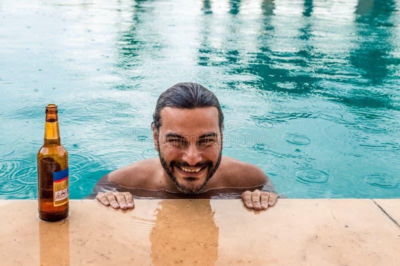 Lycklig ung man som ler med en flaska av öl i en simbassäng, medan regna arkivbild