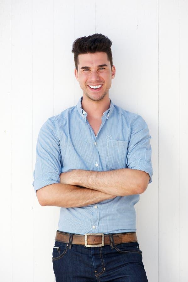 Lycklig ung man som ler mot vit bakgrund arkivbild