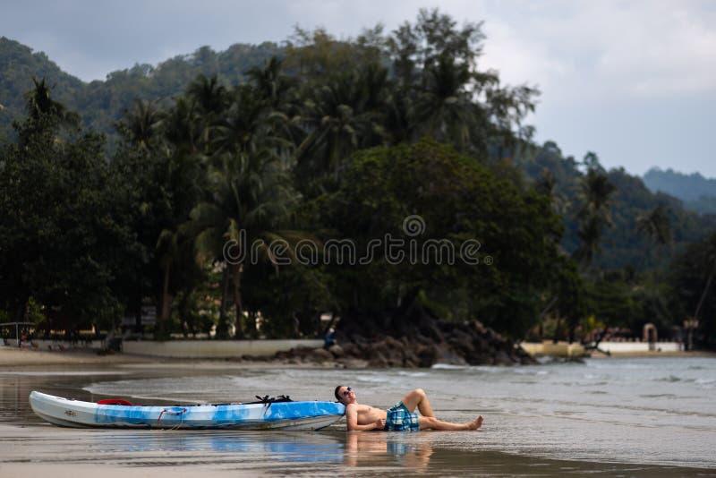 Lycklig ung man som ligger n?ra ett kajakfartyg p? Ko Chang, Thailand i April, 2018 - b?sta loppdestination f?r lycka royaltyfria bilder