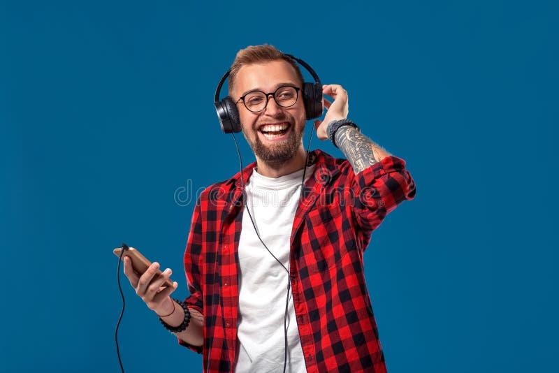 Lycklig ung man som lyssnar till musik med hörlurar Stilig le grabb i rutig skjortadans med hörlurar arkivbilder
