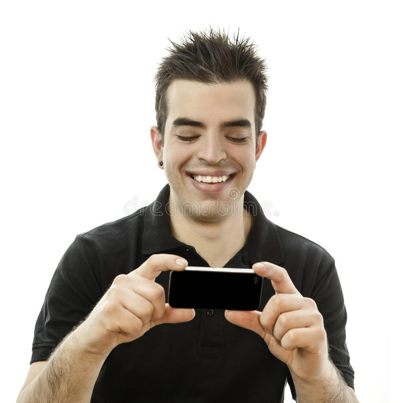 Lycklig ung man som ser hans smartphone royaltyfri foto