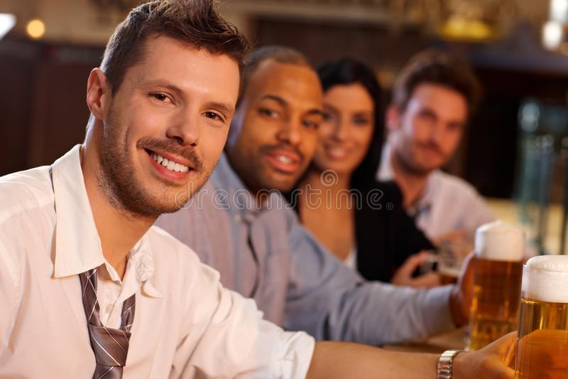 Lycklig ung man som sitter i puben, dricka öl royaltyfri bild