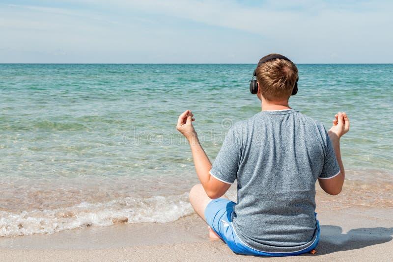 Lycklig ung man som sitter på stranden som lyssnar till musik på hörlurar koppla av yoga arkivfoton