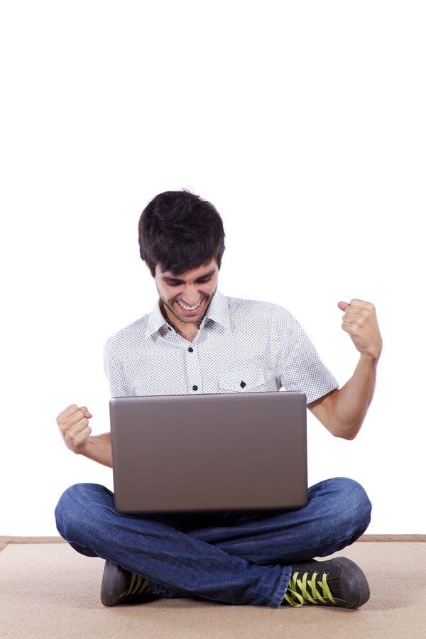 Lycklig ung man som surfar internet royaltyfri foto