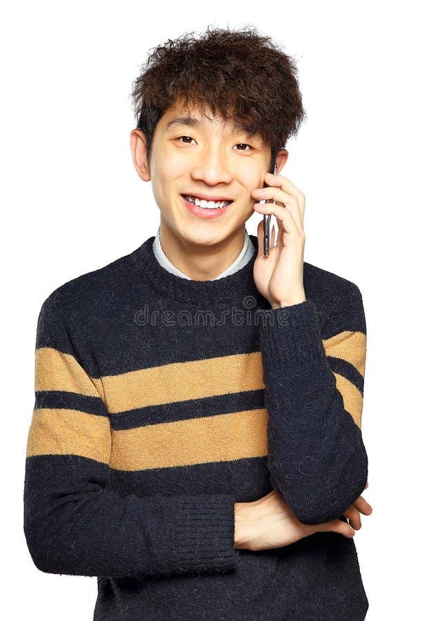 Lycklig ung man som talar på mobilephonen arkivfoto