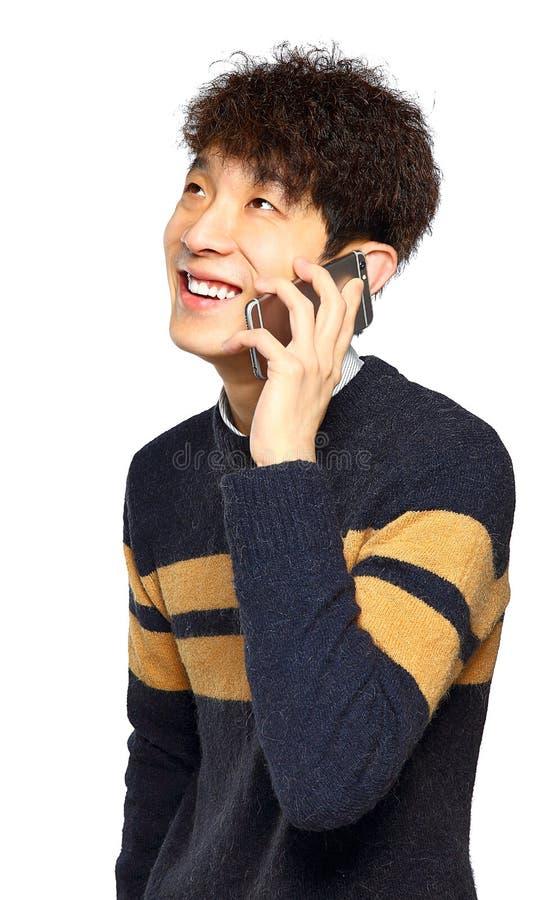 Lycklig ung man som talar på mobilephonen arkivfoton