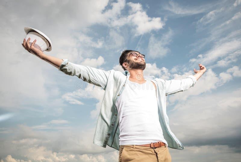 Lycklig ung man som upp till ser himlen royaltyfri bild